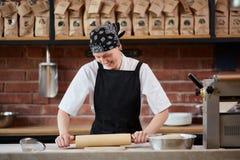Εύθυμη γυναίκα που εργάζεται με την κυλώντας καρφίτσα Στοκ Εικόνες