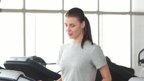 Εύθυμη γυναίκα που κάνει την καρδιο άσκηση στη γυμναστική απόθεμα βίντεο