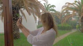 Εύθυμη γυναίκα που κάνει το καλοκαίρι selfie τη βροχερή ημέρα φιλμ μικρού μήκους