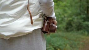 Εύθυμη γυναίκα που κρατά μια κάμερα σε μια καφετιά περίπτωση στον ώμο της στο ξύλο απόθεμα βίντεο