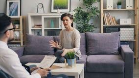 Εύθυμη γυναίκα που μιλά με την ψυχολογική συνεδρίαση συμβούλων στον καναπέ στην αρχή απόθεμα βίντεο