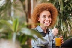 Εύθυμη γυναίκα που πίνει το χυμό από πορτοκάλι στον καφέ με τις πράσινες εγκαταστάσεις Στοκ Εικόνες