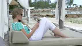 Εύθυμη γυναίκα που φορά τα γυαλιά ηλίου που κάθονται στον αργόσχολο ξενοδοχείων που χρησιμοποιεί την ψηφιακή ταμπλέτα κατά τη διά απόθεμα βίντεο