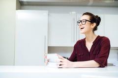 Εύθυμη γυναίκα στα γυαλιά που γελούν και που χρησιμοποιούν την ταμπλέτα στην κουζίνα Στοκ Εικόνες