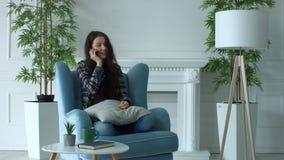 Εύθυμη γυναίκα στην πολυθρόνα που κουβεντιάζει στο έξυπνο τηλέφωνο φιλμ μικρού μήκους