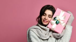 Εύθυμη γυναίκα στο γκρίζο κιβώτιο και την κατοχή δώρων εκμετάλλευσης πουλόβερ της διασκέδασης στοκ φωτογραφία