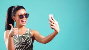 Εύθυμη γυναίκα brunette ομορφιάς στο φόρεμα και γυαλιά που θέτουν και που κάνουν selfie στο smartphone της απόθεμα βίντεο