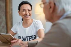 Εύθυμη εθελοντική επικοινωνία με το ανώτερο άτομο στοκ εικόνες
