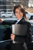 Εύθυμη επιχειρηματίας με το φάκελλο κοντά στο μαύρο αυτοκίνητο Στοκ Φωτογραφίες