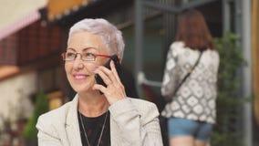 Εύθυμη επιχειρηματίας που καλεί το κινητό τηλέφωνο app στηργμένος στο θέρετρο φιλμ μικρού μήκους
