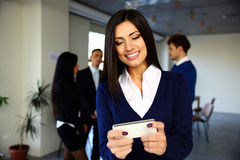 Εύθυμη επιχειρηματίας που χρησιμοποιεί το smartphone Στοκ φωτογραφία με δικαίωμα ελεύθερης χρήσης