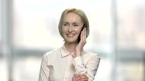 Εύθυμη επιχειρησιακή γυναίκα που μιλά στο τηλέφωνο κυττάρων απόθεμα βίντεο