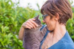 Εύθυμη εσωτερική γάτα που κατέχει και που αγκαλιάζεται η χαμογελώντας γυναίκα με eyeglasses Υπαίθρια ρύθμιση στον πράσινο εγχώριο στοκ εικόνα