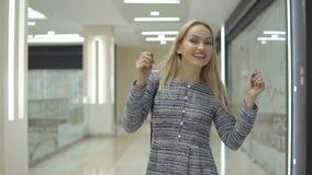 Εύθυμη ευτυχής νέα γυναίκα στους περιπάτους φορεμάτων με στη λεωφόρο απόθεμα βίντεο