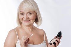 Εύθυμη ευχάριστη γυναίκα που κρατά έναν καθρέφτη Στοκ εικόνα με δικαίωμα ελεύθερης χρήσης