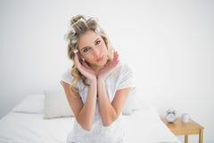 Εύθυμη ελκυστική ξανθή τοποθέτηση ρόλερ τρίχας φθοράς Στοκ Φωτογραφία