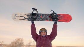 Εύθυμη ηλικιωμένη γυναίκα που αυξάνεται επάνω στο σνόουμπορντ στη χιονώδη κλίση στο χειμερινό θέρετρο απόθεμα βίντεο