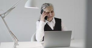 Εύθυμη ηλικιωμένη γυναίκα που μιλά σε ένα κινητό τηλέφωνο στο γραφείο γραφείων απόθεμα βίντεο