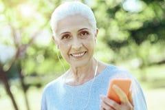 Εύθυμη ηλικιωμένη γυναίκα που φορά τα ακουστικά Στοκ Εικόνες