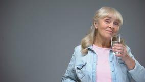 Εύθυμη ηλικιωμένη κυρία που παίρνει το ενάντιο στον ιό χάπι, ασυλία που ενισχύει, υγειονομική περίθαλψη φιλμ μικρού μήκους