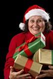 Εύθυμη ηλικιωμένη κυρία που προσφέρει τρία τυλιγμένα δώρα στοκ εικόνες