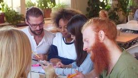 Εύθυμη διαφορετική διεθνής ομάδα σπουδαστών που κουβεντιάζει και που εργάζεται μαζί στον καφέ απόθεμα βίντεο