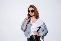 Εύθυμη κυρία που φορά τα γυαλιά ηλίου που τεντώνουν τη γόμμα φυσαλίδων Στοκ Φωτογραφίες