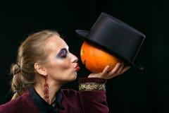 Εύθυμη μάγισσα κοριτσιών σε αποκριές με την κολοκύθα Στοκ Φωτογραφίες