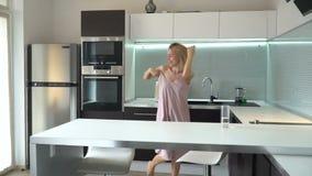 Εύθυμη μέσης ηλικίας γυναίκα που χορεύει στην κουζίνα απόθεμα βίντεο