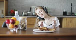 Εύθυμη μαθήτρια με τα ακουστικά που κάθεται στον πίνακα στην κουζίνα και το χορό απόθεμα βίντεο
