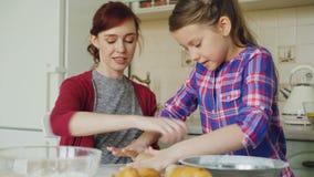 Εύθυμη μητέρα και χαριτωμένη κυλώντας ζύμη κορών μαγειρεύοντας στην κουζίνα στο Σαββατοκύριακο Οικογένεια, τρόφιμα, σπίτι και άνθ φιλμ μικρού μήκους