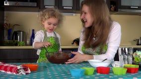 Εύθυμη μητέρα με τη χαριτωμένη παιδιών ζύμη σοκολάτας κοριτσιών δοκιμάζοντας από το δάχτυλο και το φιλί φιλμ μικρού μήκους