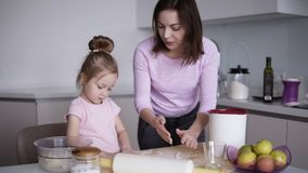 Εύθυμη μητέρα με το παιδί της, ένα κορίτσι που έχει τη διασκέδαση προετοιμάζοντας ένα κέικ στη σύγχρονη, άσπρη κουζίνα τους Παίζο φιλμ μικρού μήκους