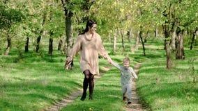 Εύθυμη μητέρα με το παιχνίδι αγοράκι στο πάρκο φθινοπώρου Όμορφη γυναίκα που κρατά το γιο νηπίων της υπαίθρια φιλμ μικρού μήκους