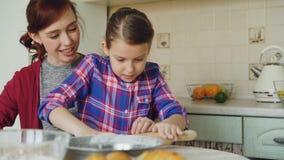 Εύθυμη μητέρα που μιλά στην αναμιγνύοντας και κυλώντας ζύμη χαριτωμένων κορών μαγειρεύοντας στην κουζίνα στο Σαββατοκύριακο Οικογ απόθεμα βίντεο