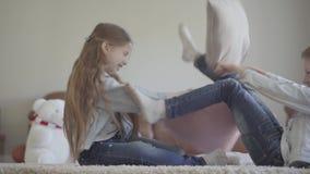 Εύθυμη μικρή φιλική πάλη κοριτσιών και αγοριών διδύμων στο καθιστικό με τα μαξιλάρια στα ίδια ενδύματα και γέλιο φιλμ μικρού μήκους