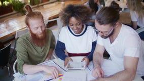 Εύθυμη μικτή διεθνής ομάδα σπουδαστών που κουβεντιάζει και που εργάζεται μαζί στον καφέ φιλμ μικρού μήκους