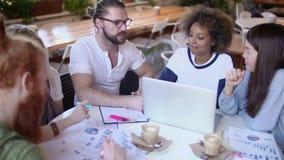Εύθυμη μικτή διεθνής ομάδα σπουδαστών που κουβεντιάζει και που εργάζεται στο lap-top μαζί στον ευρωπαϊκό καφέ απόθεμα βίντεο