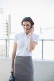 Εύθυμη μοντέρνη καφετιά μαλλιαρή επιχειρηματίας που κάνει ένα τηλεφώνημα Στοκ Εικόνα
