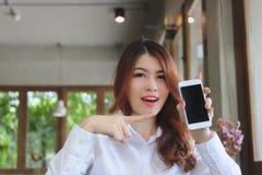 Εύθυμη νέα ασιατική επιχειρησιακή γυναίκα που κρατά το κινητό έξυπνο τηλέφωνο στο καθιστικό στοκ φωτογραφίες