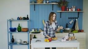 Εύθυμη νέα αστεία γυναίκα που χορεύει και σύνολο τραγουδιού ο πίνακας για το πρόγευμα στην κουζίνα στο σπίτι απόθεμα βίντεο