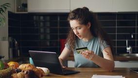 Εύθυμη νέα γυναίκα που έχει on-line να ψωνίσει χρησιμοποιώντας το φορητό προσωπικό υπολογιστή και την πιστωτική κάρτα ενώ έχει το απόθεμα βίντεο