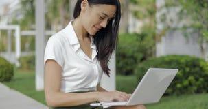 Εύθυμη νέα γυναίκα που χρησιμοποιεί το lap-top απόθεμα βίντεο