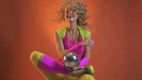 Εύθυμη νέα γυναίκα στην εξάρτηση της δεκαετίας του '80, με μια μικρή σφαίρα disco, που τινάζει το κεφάλι της και που παίζει με τη φιλμ μικρού μήκους