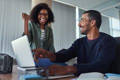 Εύθυμη νέα επιχειρηματίας που γιορτάζει την επιτυχία τους στοκ εικόνα