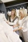 Εύθυμη νέα κόρη με την ανώτερη μητέρα που επιλέγει το γαμήλιο φόρεμα στη νυφική μπουτίκ Στοκ Φωτογραφία