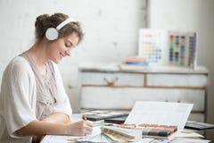 Εύθυμη νέα μουσική ακούσματος γυναικών στην εργασία Στοκ φωτογραφία με δικαίωμα ελεύθερης χρήσης