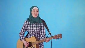 Εύθυμη νέα μουσουλμανική γυναίκα που παίζει εκφραστικά την κιθάρα σε ένα μπλε υπόβαθρο απόθεμα βίντεο