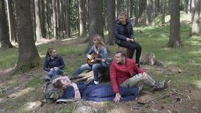Εύθυμη νέα ομάδα τροχόσπιτων εφήβων στα ξύλα που έχουν την κιθάρα παιχνιδιού διασκέδασης που τραγουδά και που παίρνει selfie - απόθεμα βίντεο