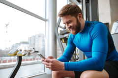 Εύθυμη νέα συνεδρίαση αθλητικών τύπων στη γυμναστική και εξέταση το τηλέφωνο Στοκ φωτογραφίες με δικαίωμα ελεύθερης χρήσης